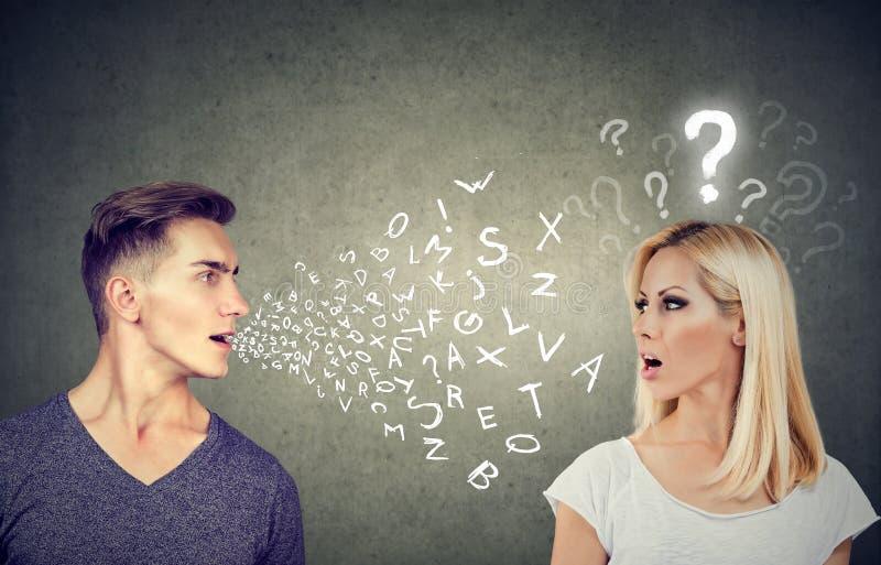 语言障隘概念 英俊的人谈话与有问号的一名可爱的妇女 库存图片