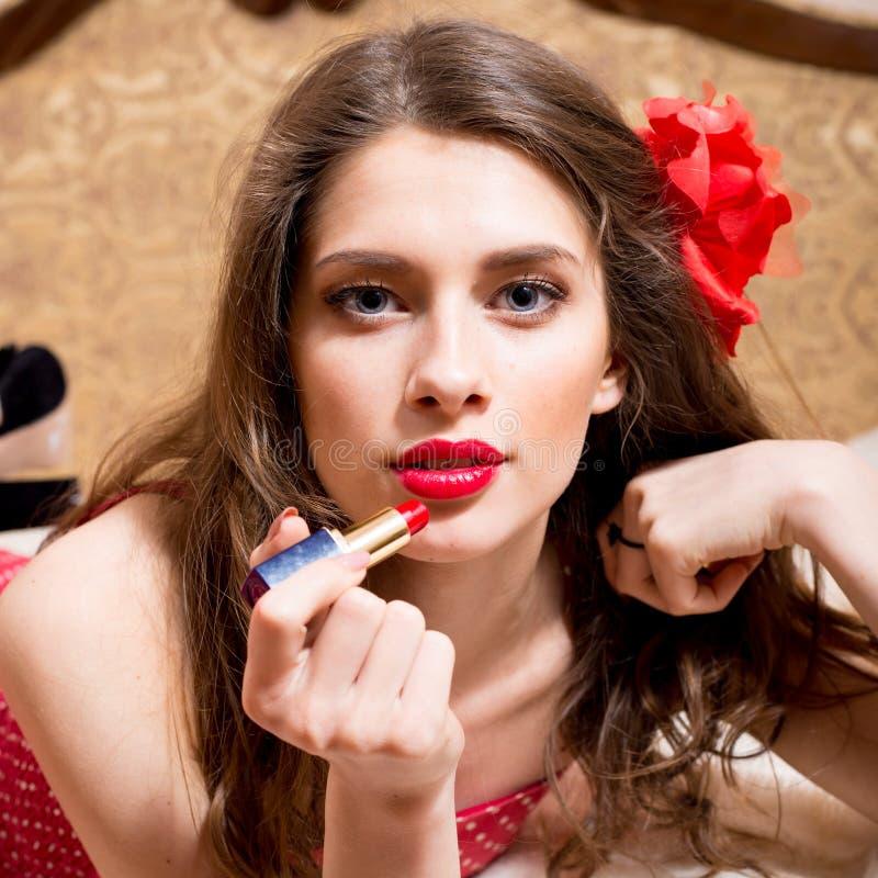 诱人的可爱的性画报女孩特写镜头画象有红色花的在头发画红色唇膏开放嘴唇肉欲上 免版税库存图片