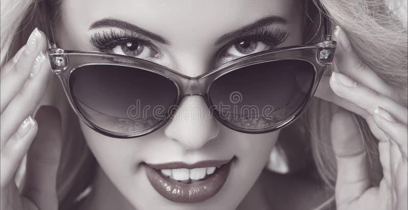 诱人的妇女佩带的太阳镜 库存照片