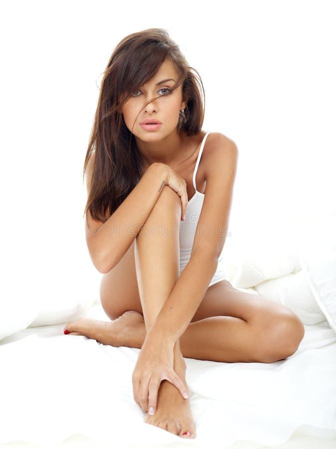 诱人的妇女坐白色床 免版税图库摄影