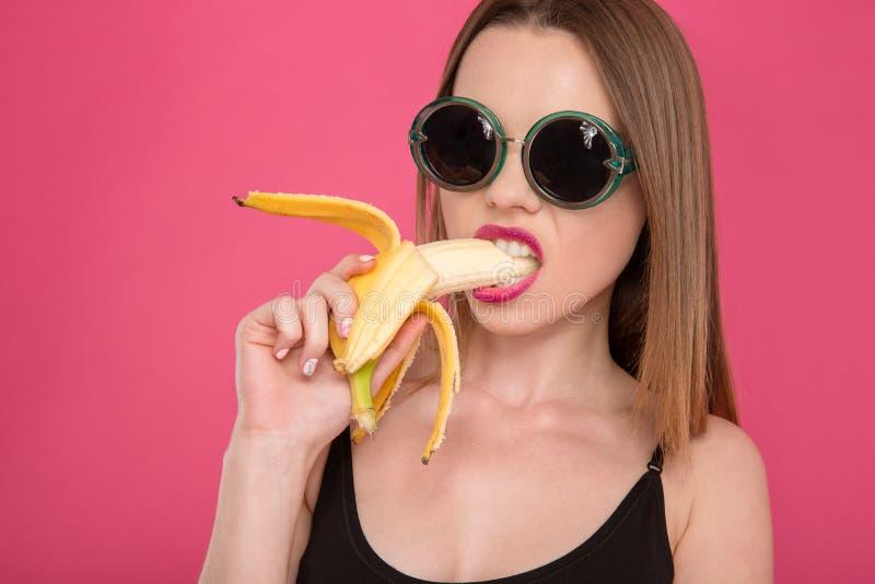 年轻诱人的式样吃香蕉特写镜头  免版税库存照片