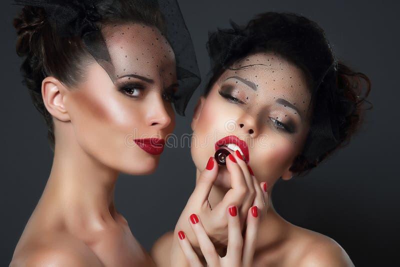 诱剂 两名诱人的妇女用樱桃莓果 免版税库存照片