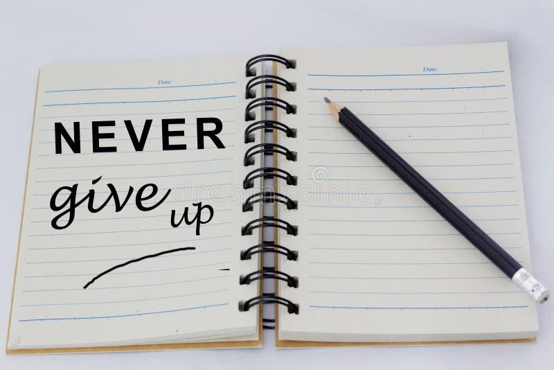 诱导词在一个被打开的笔记本的一页从未给赞扬有铅笔的在它旁边 图库摄影