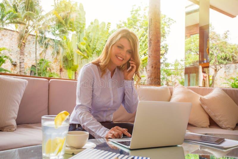 说在电话里和使用便携式计算机的女商人 免版税库存照片