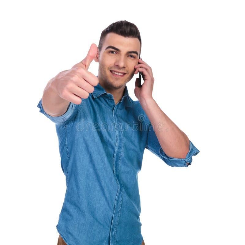 说在电话里和做好标志的年轻人 免版税库存照片