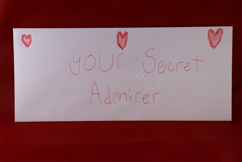 说情人节的信封您的有在笔和红色背景画的红色心脏的秘密钦佩者 免版税库存照片