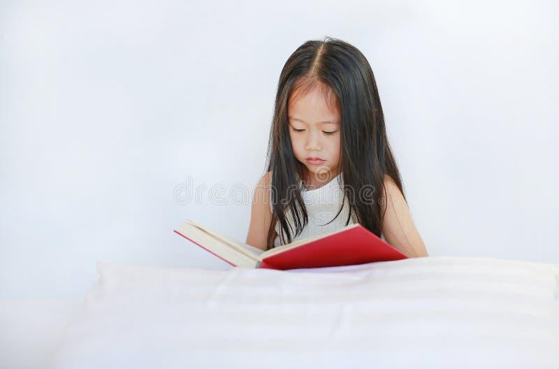 说谎与在白色背景的枕头的美丽的矮小的亚洲儿童女孩读书精装书 免版税图库摄影