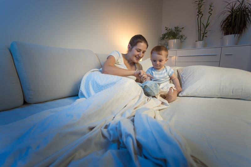 说谎与她的小儿子在床上和给他长毛绒玩具的年轻母亲 图库摄影