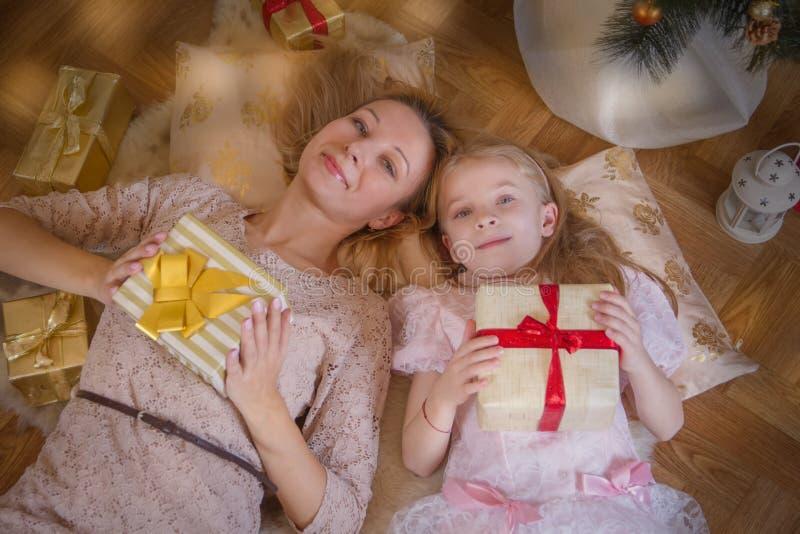 说谎与礼物的母亲和女儿在圣诞树下 图库摄影