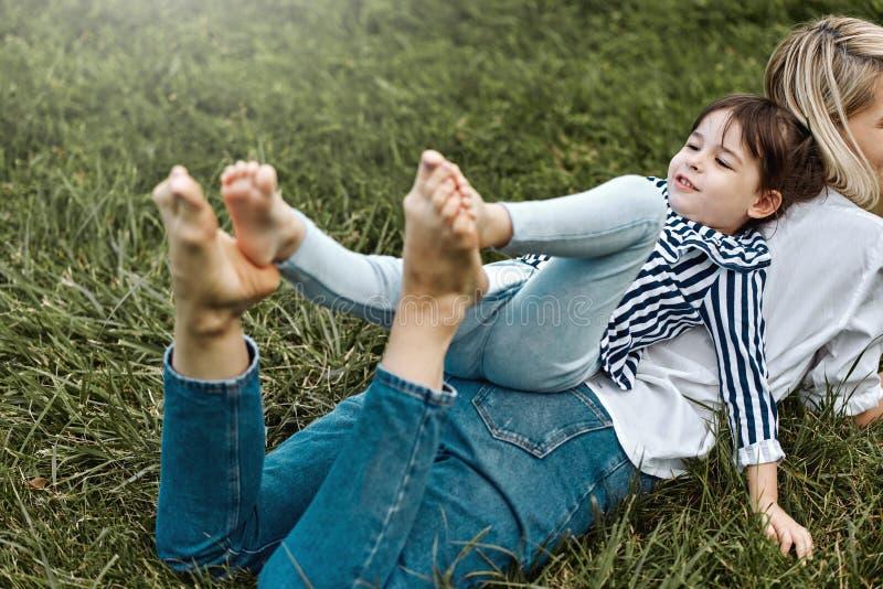 说谎和使用与她绿草户外的逗人喜爱的女孩的美女的水平的图象 愉快的孩子和 图库摄影