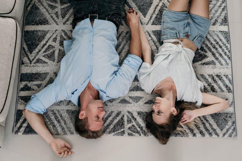 说谎和放松在地毯的富感情的夫妇 库存图片