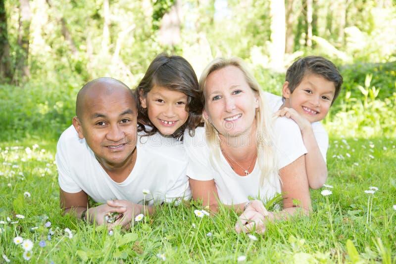 说谎和放松在绿色公园的混合的族种家庭在美好的夏日 图库摄影