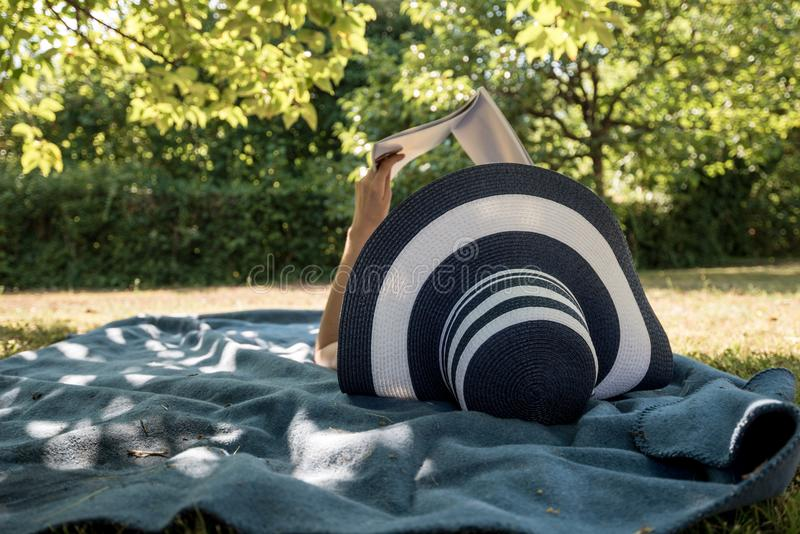 说谎在一个地毯的妇女在读书的树的树荫下 免版税图库摄影
