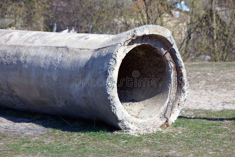 说谎在一个绿色管子的一个大老灰色具体管子外面 免版税库存图片