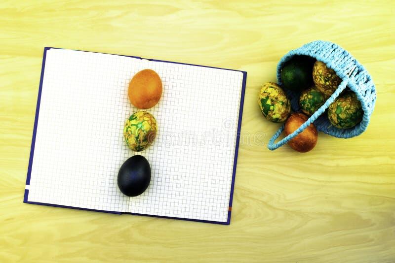说谎在一个蓝色篮子和在一张黄色木桌、一本书笔记的作为浆糊的拷贝和鸡蛋上的复活节彩蛋说谎对此 免版税库存照片