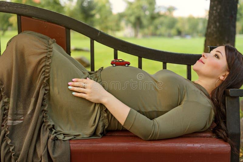 说谎在一个长凳和一辆小的红色汽车立场的年轻人孕妇在她的腹部 免版税库存图片