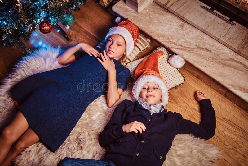 说谎在一张毛皮地毯的顶视图、兄弟和姐妹在为圣诞节装饰的客厅 免版税库存图片