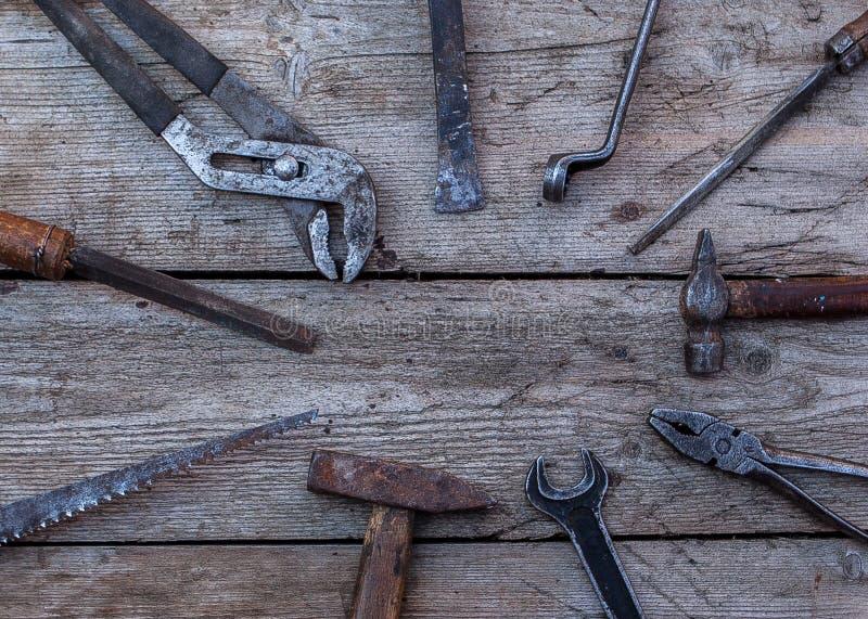 说谎在一张黑木桌上的老,生锈的工具 锤子,凿子,引形钢锯,金属板钳 复制空间 免版税图库摄影