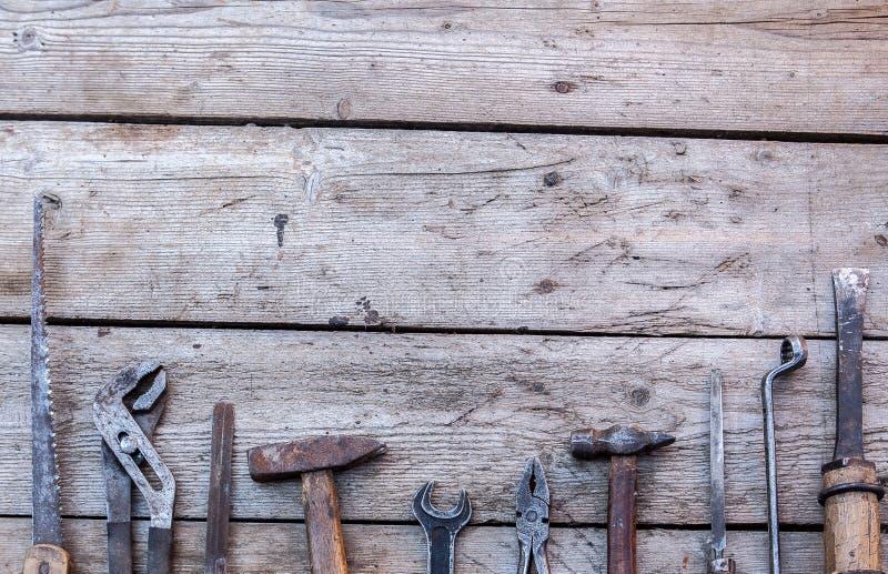 说谎在一张黑木桌上的老,生锈的工具 锤子,凿子,引形钢锯,金属板钳 复制空间 免版税库存图片