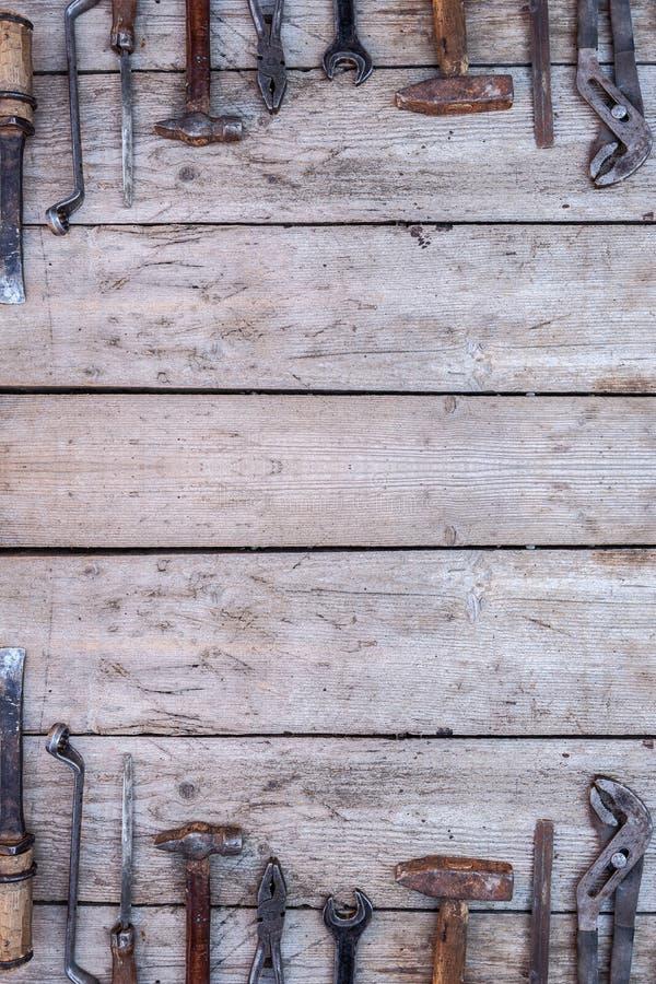 说谎在一张黑木桌上的老,生锈的工具 锤子,凿子,引形钢锯,金属板钳 r 免版税库存图片