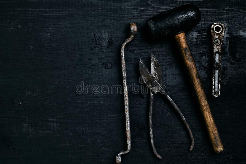 说谎在一张黑木桌上的老,生锈的工具 锤子,凿子,金属剪,板钳 免版税库存照片