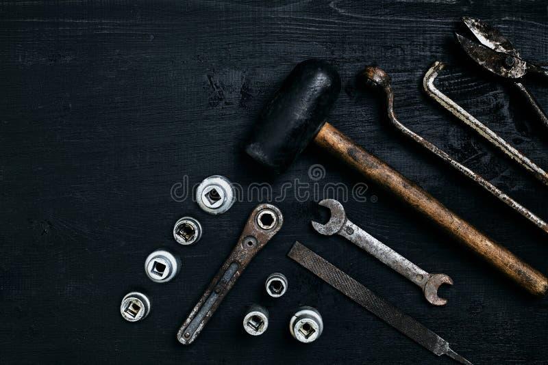 说谎在一张黑木桌上的老,生锈的工具 锤子,凿子,金属剪,板钳 免版税图库摄影