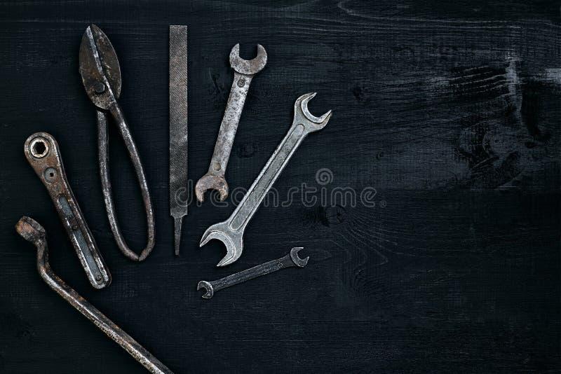 说谎在一张黑木桌上的老,生锈的工具 锤子,凿子,金属剪,板钳 图库摄影