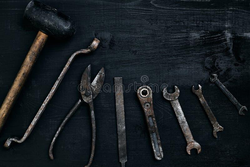 说谎在一张黑木桌上的老,生锈的工具 锤子,凿子,金属剪,板钳 免版税库存图片