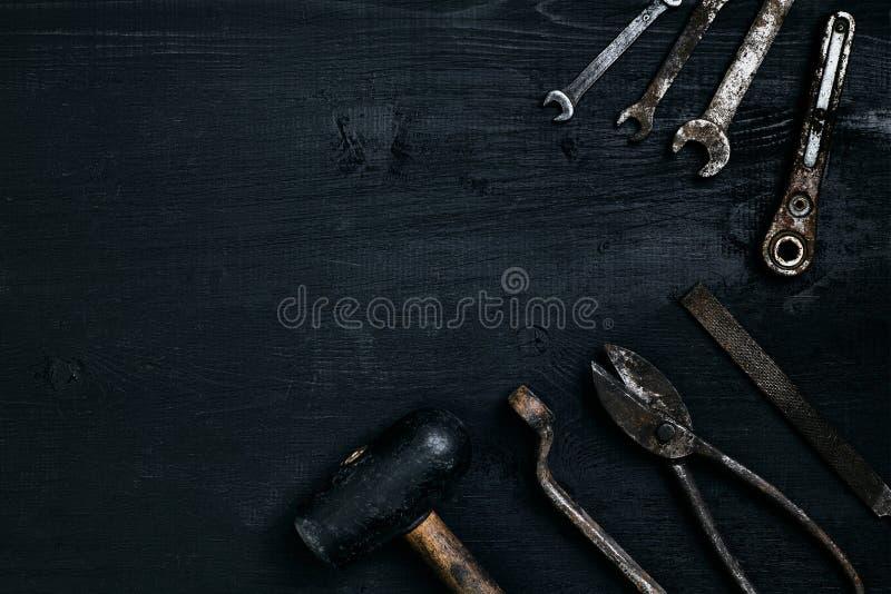 说谎在一张黑木桌上的老,生锈的工具 锤子,凿子,金属剪,板钳 库存照片