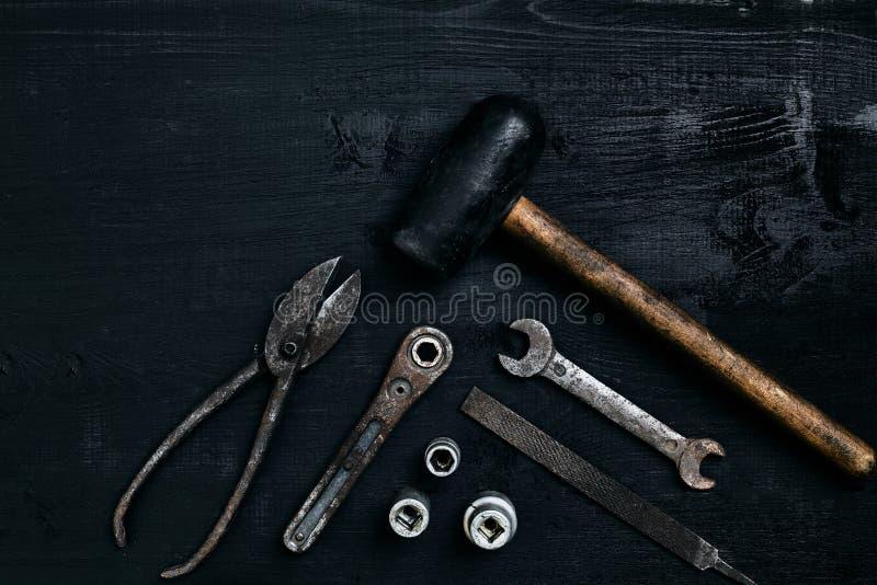 说谎在一张黑木桌上的老,生锈的工具 锤子,凿子,金属剪,板钳 库存图片