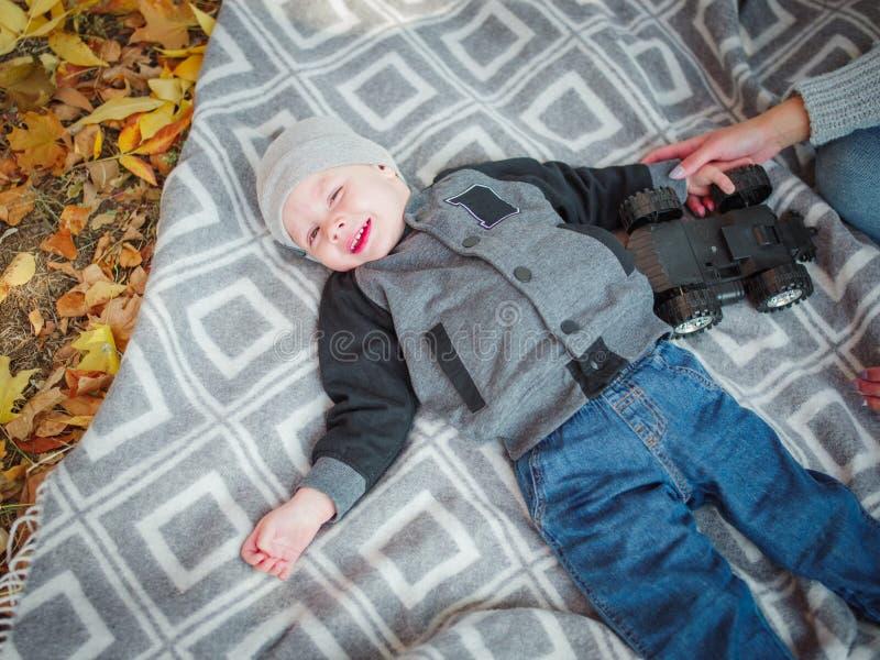 说谎在一条毯子的逗人喜爱的矮小的男婴在秋天公园 免版税图库摄影