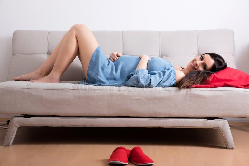 说谎在一身庄重装束的一个沙发的一名微笑的孕妇 库存照片