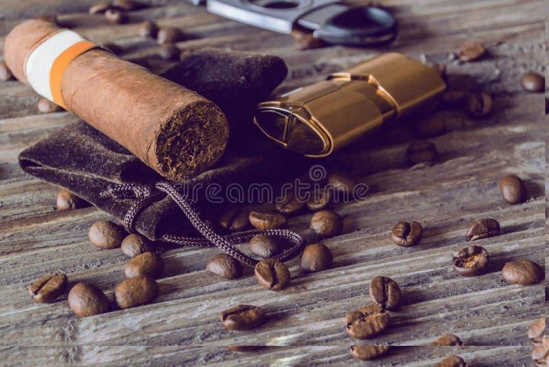 说谎在与一个断头台和雪茄打火机的一个布料袋子的雪茄在用烤咖啡豆盖的一张老木质地桌上 库存图片