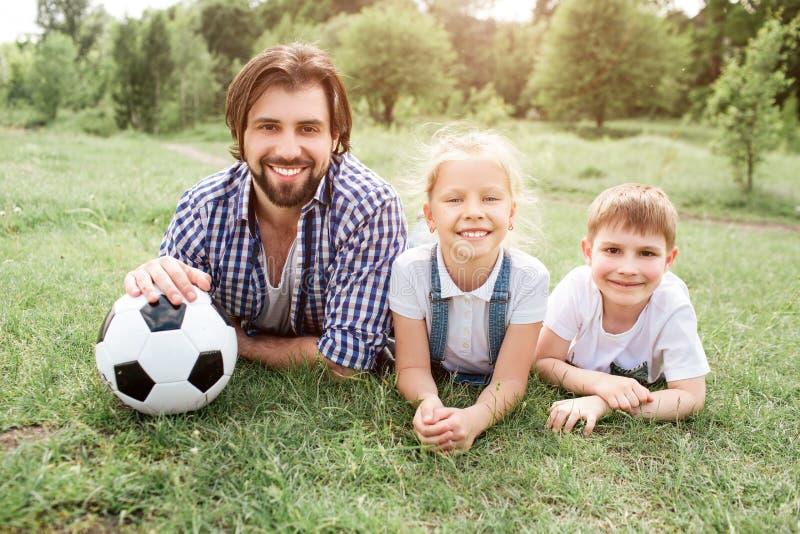 说谎在与他的孩子的草的父亲的图片 他拿着除他自己以外的球 他们在照相机amd看 库存照片