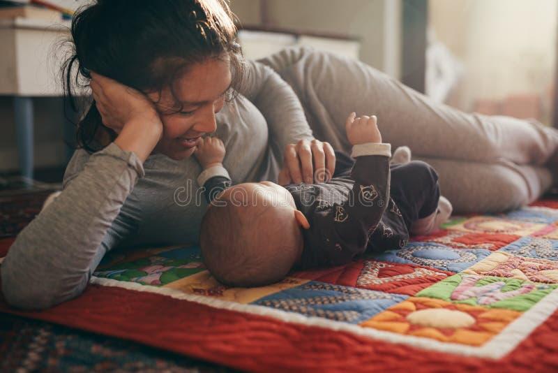 说谎在与她的婴孩的床上的母亲 免版税库存照片