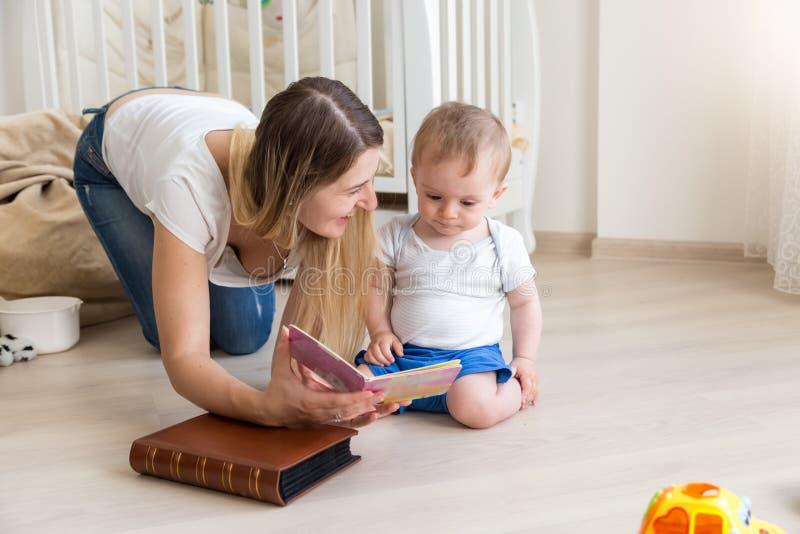 说谎在与她的小孩男孩和阅读书的地板上的年轻母亲 免版税图库摄影