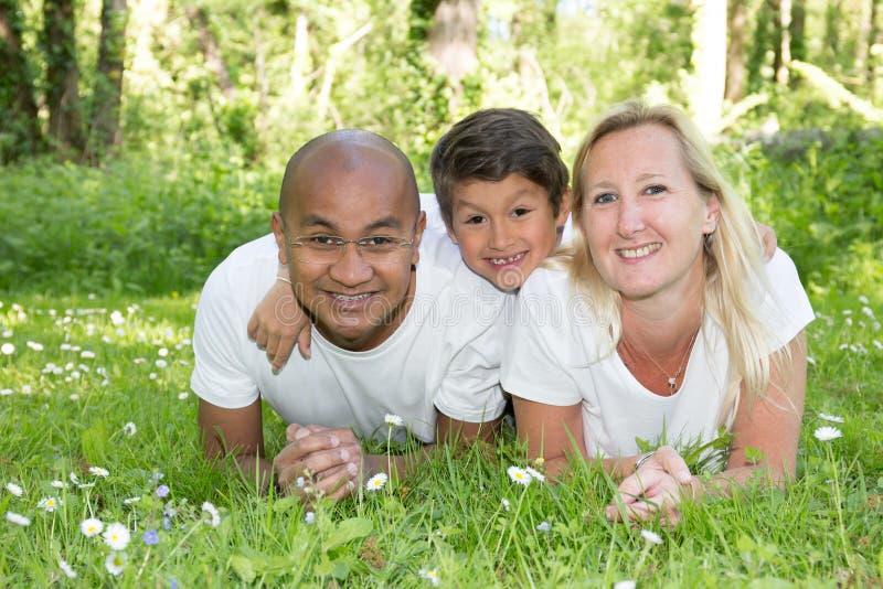 说谎在与孩子的草的不同种族的家庭 微笑的加上儿子和看照相机 母亲和黑人父亲庭院的 图库摄影