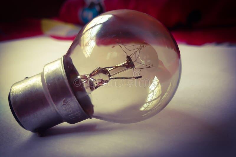 说谎在与小插图作用葡萄酒摄影的一张纸的电灯泡 库存照片