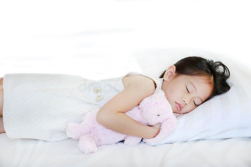 说谎在与拥抱玩偶的床上的睡觉的小亚裔孩子女孩 免版税库存图片