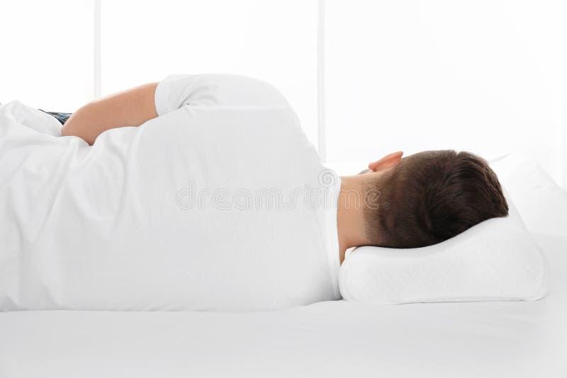 说谎在与矫形枕头的床上的年轻人 免版税库存照片
