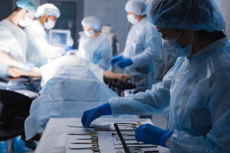 说谎在与近护士和外科医生的桌上的外科工具在背景 免版税图库摄影
