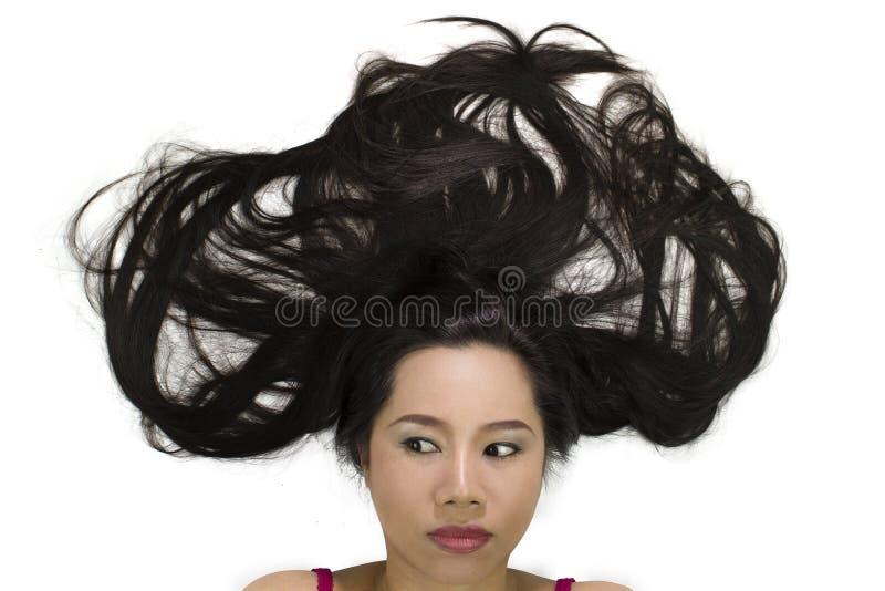 说谎在与黑长发的地面的喜怒无常的亚裔妇女特写镜头画象  行动生气,不快乐 库存图片