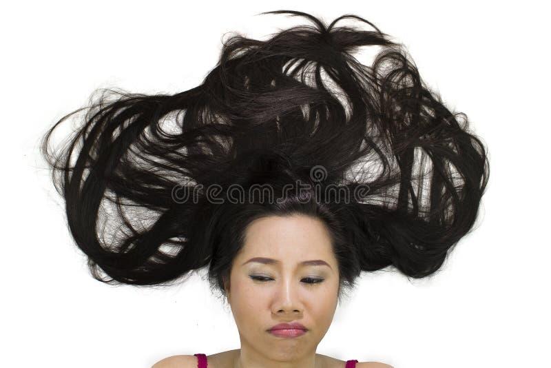 说谎在与黑长发的地面的喜怒无常的亚裔妇女特写镜头画象  行动生气,不快乐 免版税图库摄影