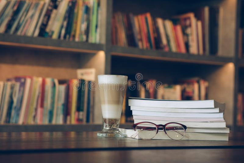 说谎在书和咖啡饮料的镜片在有拷贝空间的图书馆屋子里文本的反对书架在背景中 ?? 库存图片