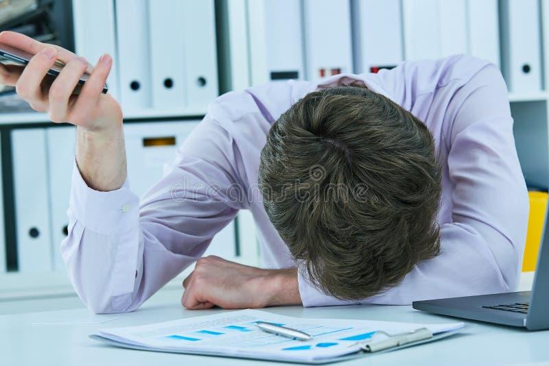 说谎在书桌上的年轻商人在拿着智能手机的办公室,保留在他的手上的面孔 最后期限概念 时间 免版税库存图片