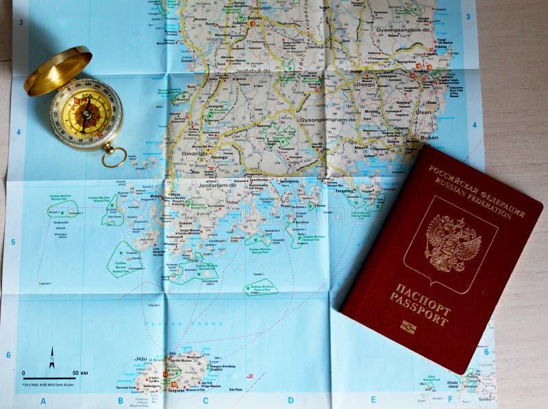 说谎在地图的旅行护照和金黄指南针 库存照片