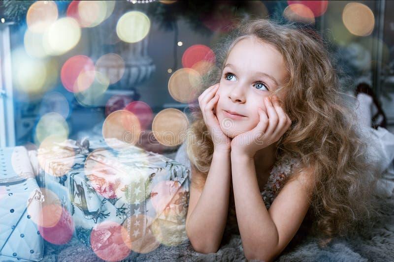 说谎在地板上在圣诞树附近和看在玩具的可爱的矮小的白肤金发的女孩 库存图片