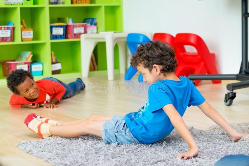 说谎在地板上的两个男孩孩子和在学龄前图书馆,幼儿园学校教育概念里一起使用 变化孩子 免版税库存图片