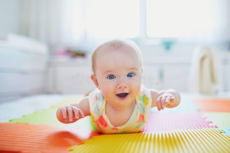 说谎在地板上的五颜六色的戏剧席子的女婴 库存照片