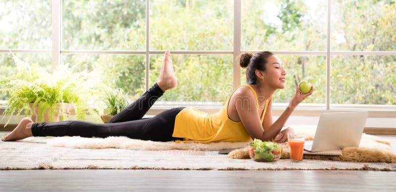 说谎在地板上的健康亚裔妇女吃看起来的沙拉轻松和舒适 库存照片